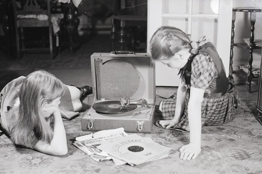 Foto in bianco e nero di due ragazze vicino a un fonografo con una piccola pila di CD audio tra di loro.