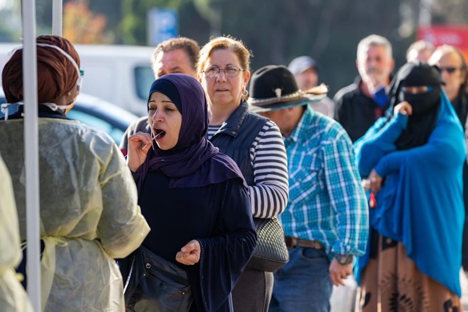 Una donna si mette in bocca un tampone per il test Covid-19 mentre altri si mettono in fila dietro di lei in un sito di test pop-up.  Fonte: Getty