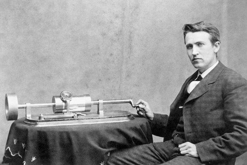 Una foto in bianco e nero di un giovane Thomas Edison seduto a un tavolo su cui è seduto uno dei suoi fonografi.