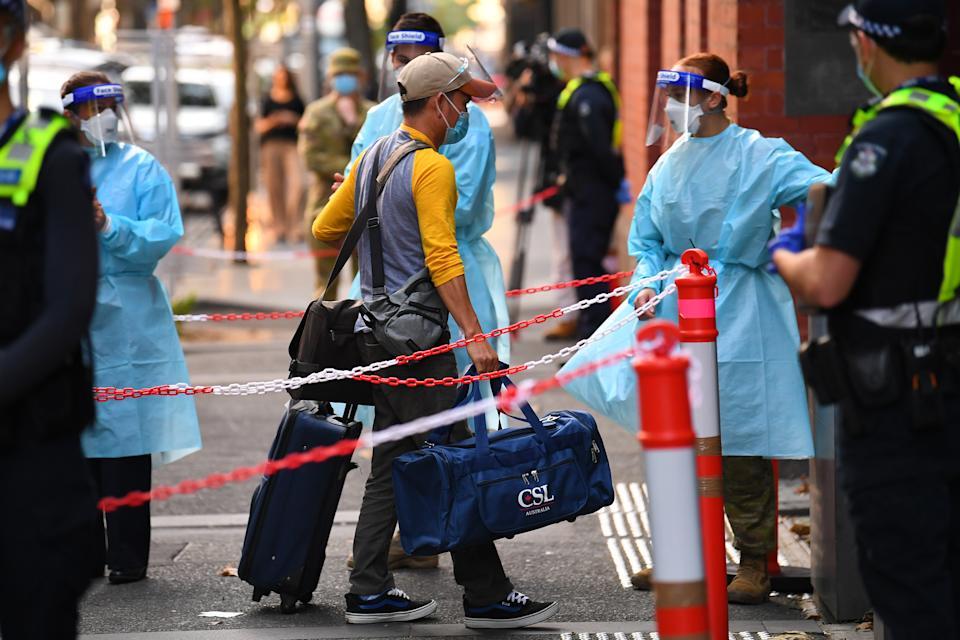 Un viaggiatore di ritorno (al centro) esce dallo Skybus all'arrivo all'Intercontinental Quarantine Hotel di Melbourne.  Fonte: AAP