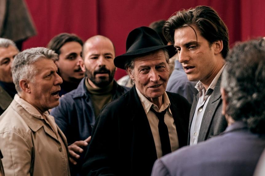 Carlo Seschi e Luca Marnelli stanno in mezzo a una folla di persone che parlano al Martin Eden