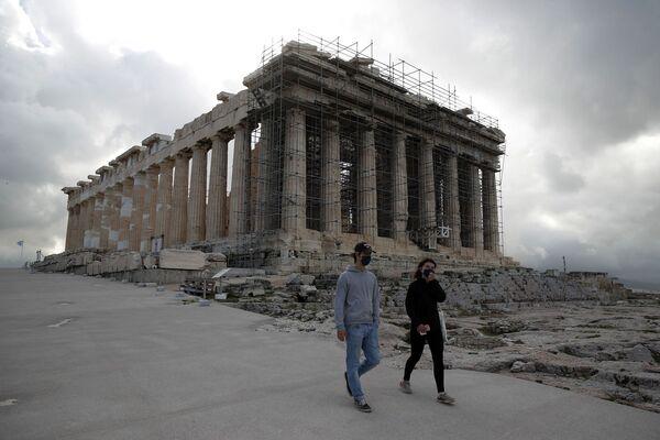 I visitatori che indossano maschere per il viso salgono sulla collina dell'Acropoli, con il Partenone sullo sfondo di Atene.  File immagine: AP Photo / Thanassis Stavrakis