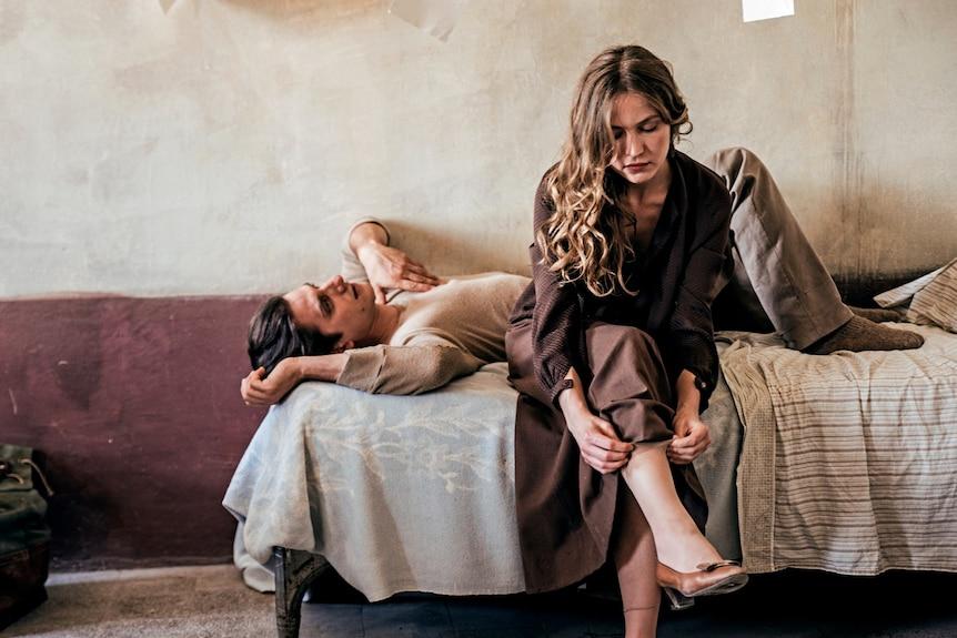 Luca Marnelli giace su un letto mentre Jessica Cressi si siede sul bordo mentre si infila il calzino in Martin Eden