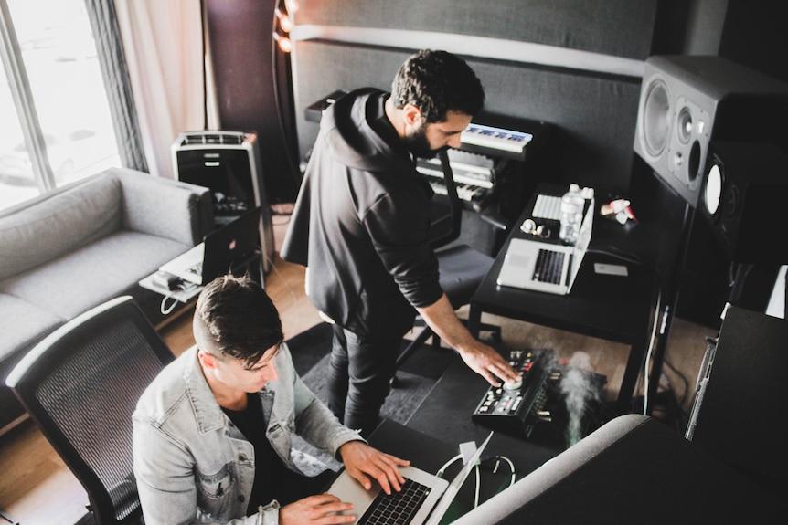 Due uomini che lavorano su apparecchiature musicali in uno studio di registrazione