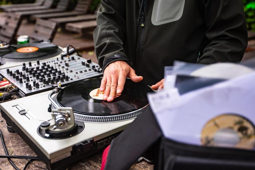 DJ mixa canzoni usando vinile e giradischi.